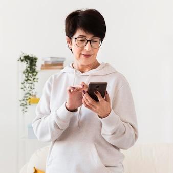 Vista frontale della donna che esamina smartphone