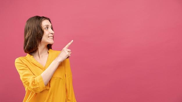 Vista frontale della donna che indica in su con lo spazio della copia