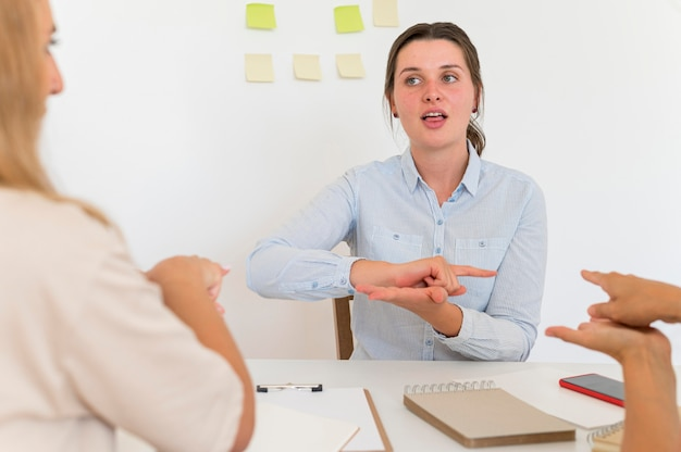 Vista frontale della donna che insegna la lingua dei segni