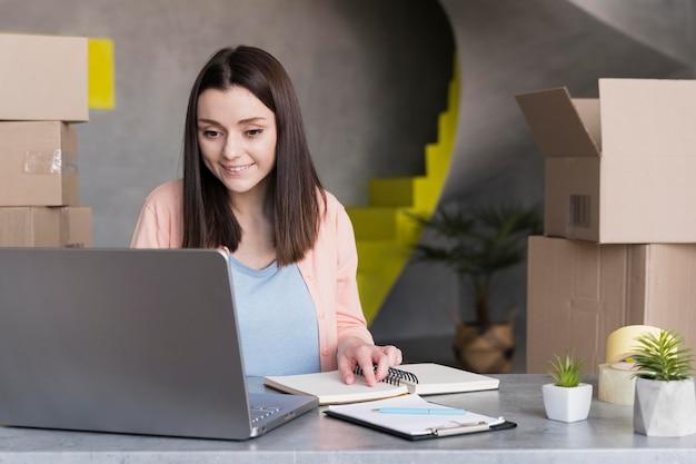 Vista frontale della donna che lavora al computer portatile con le scatole nella parte posteriore
