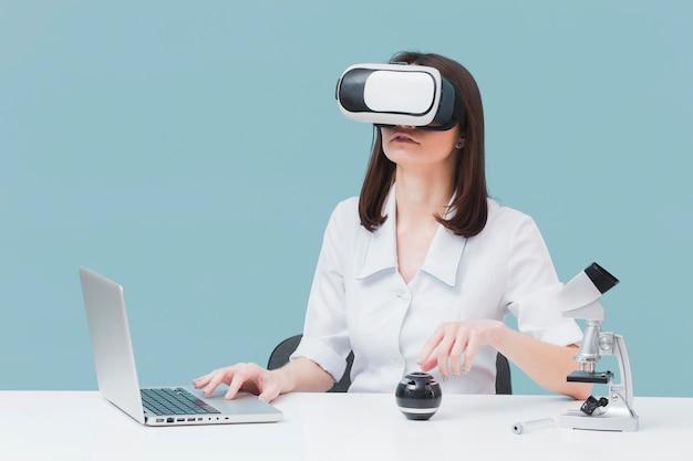 Vista frontale della donna che per mezzo del computer portatile e della cuffia avricolare di realtà virtuale