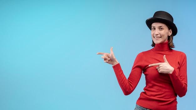 Vista frontale della donna che posa con il cappello mentre indicando