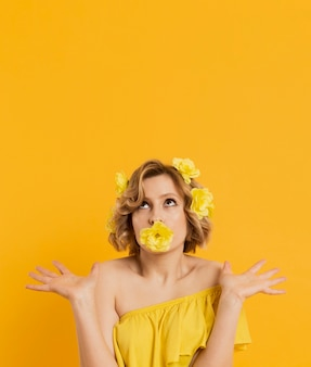 Vista frontale della donna che posa con il fiore che copre la sua bocca