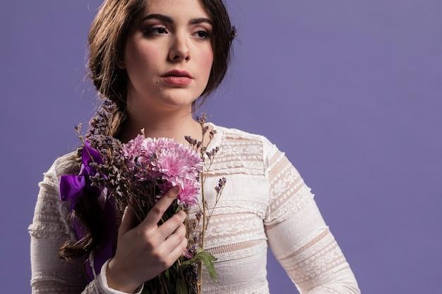 Vista frontale della donna che posa con il mazzo dei fiori