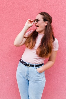Vista frontale della donna che posa mentre indossando gli occhiali da sole