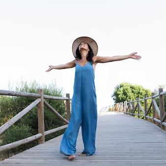 Vista frontale della donna che posa spensierata sul ponte all'aperto