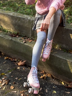 Vista frontale della donna che posa sulle scale con calzini e pattini a rotelle