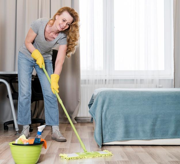 Vista frontale della donna che pulisce felicemente il pavimento