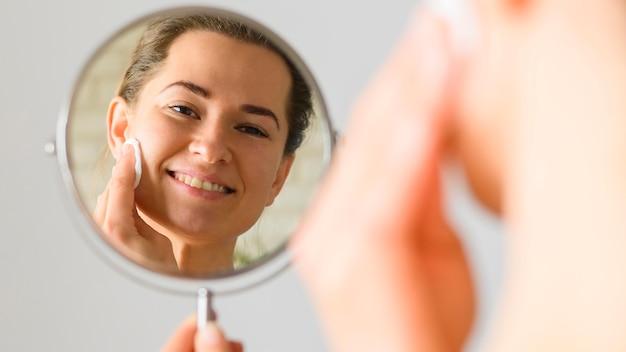 Vista frontale della donna che pulisce il suo viso allo specchio