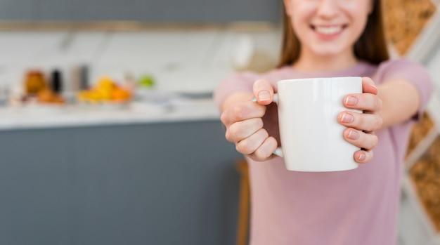 Vista frontale della donna che tiene tazza con cucina sfocato