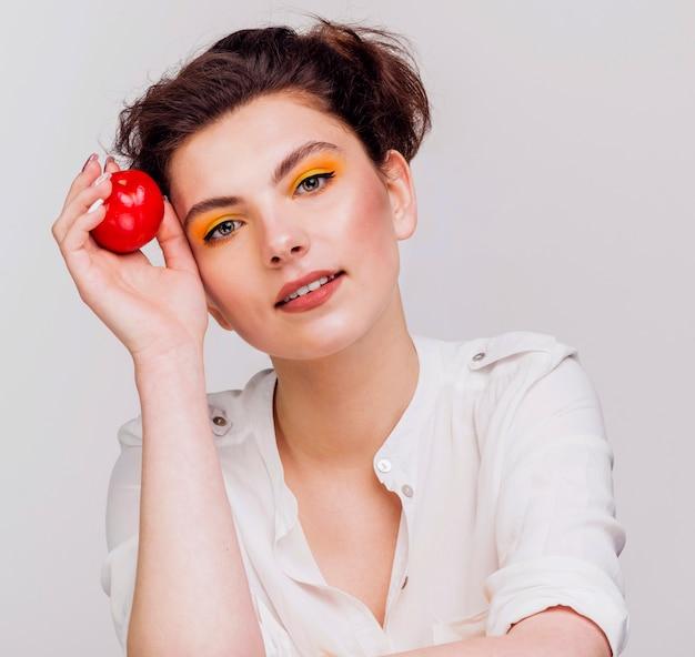 Vista frontale della donna che tiene una mela