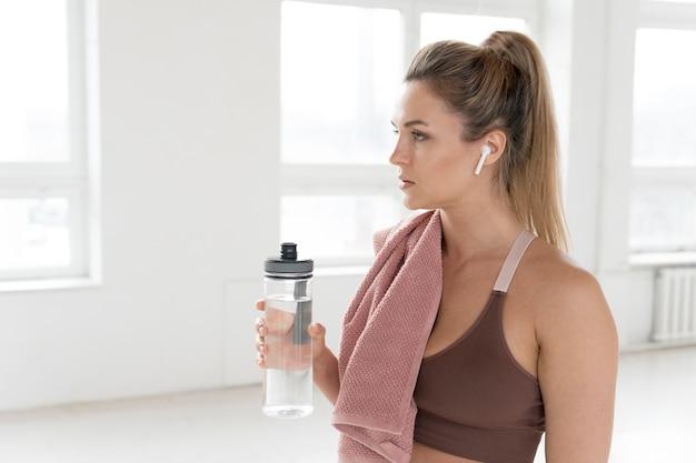 Vista frontale della donna con asciugamano e bottiglia d'acqua