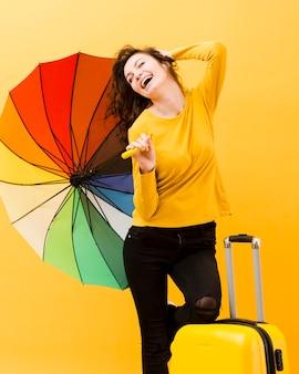 Vista frontale della donna con l'ombrello dell'arcobaleno