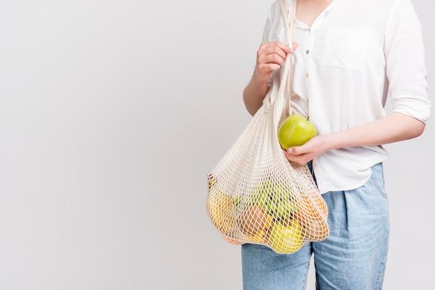 Vista frontale della donna con la borsa dei frutti