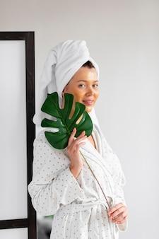 Vista frontale della donna con la cura della pelle sul viso tenendo la foglia della pianta