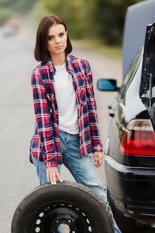 Vista frontale della donna con la gomma di automobile