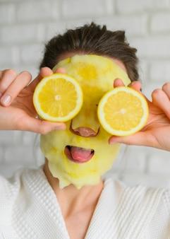 Vista frontale della donna con la maschera che posa con le fette del limone