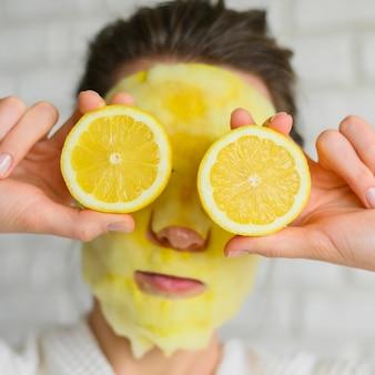Vista frontale della donna con la maschera per il viso che tiene le fette di limone