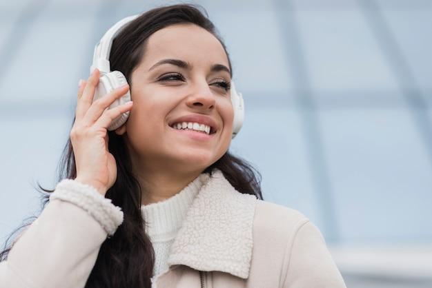Vista frontale della donna di smiley che ascolta la musica sulle cuffie