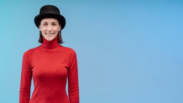 Vista frontale della donna di smiley che propone con lo spazio della copia e del cappello