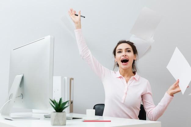 Vista frontale della donna estatica alle carte di lancio del lavoro