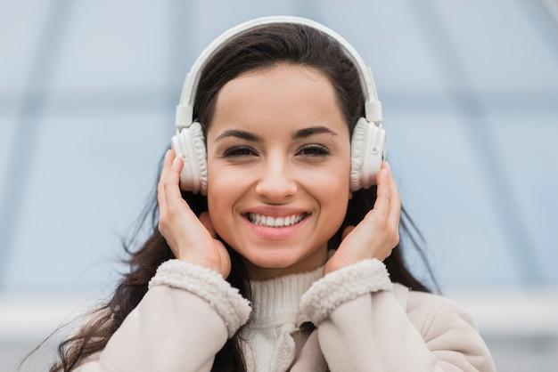 Vista frontale della donna felice che ascolta la musica sulle cuffie
