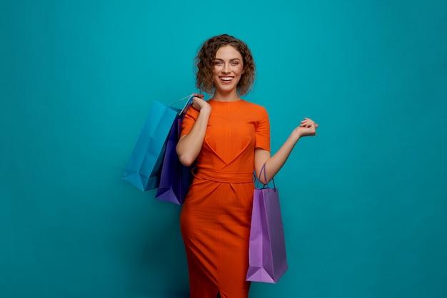 Vista frontale della donna felice che mantiene i sacchi di carta variopinti