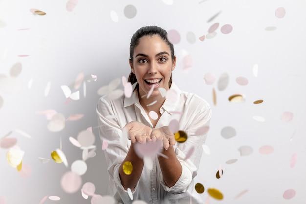 Vista frontale della donna felice con i coriandoli