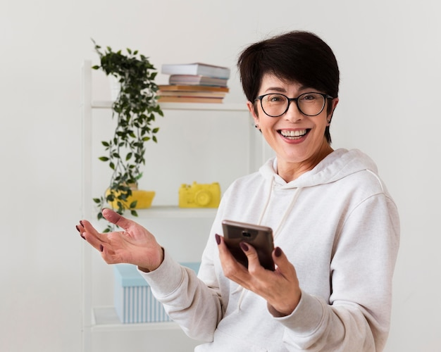 Vista frontale della donna felice con lo smartphone