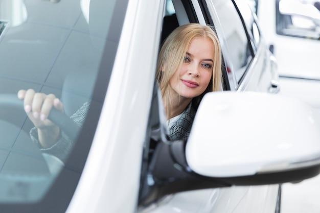 Vista frontale della donna in automobile bianca