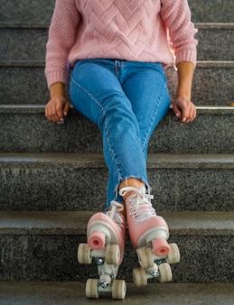 Vista frontale della donna in jeans con pattini a rotelle