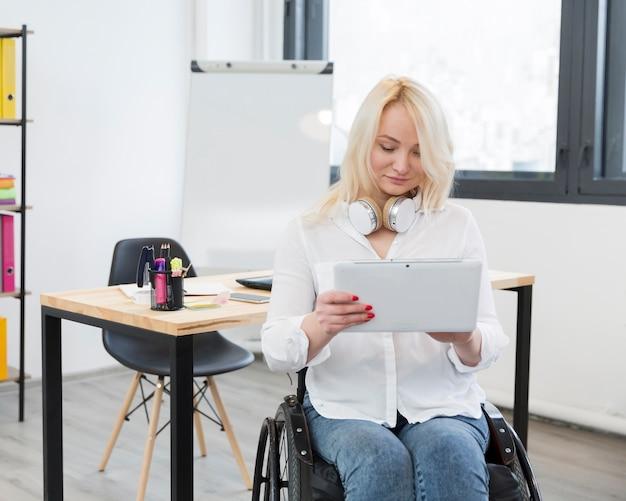 Vista frontale della donna in sedia a rotelle alla compressa della tenuta dell'ufficio