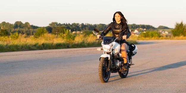 Vista frontale della donna in sella a una motocicletta senza preoccupazioni