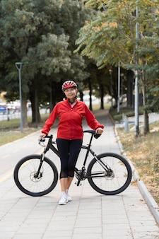 Vista frontale della donna maggiore che propone all'aperto con la bici