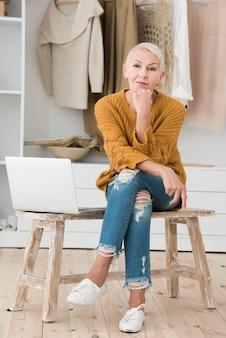 Vista frontale della donna matura che posa con il computer portatile sulla sedia