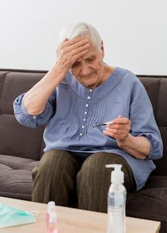 Vista frontale della donna più anziana che controlla il suo termometro