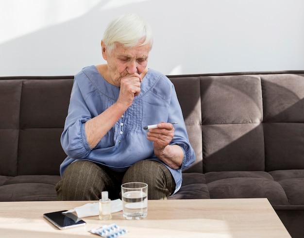 Vista frontale della donna più anziana che esamina termometro