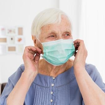Vista frontale della donna più anziana che posa con la maschera medica