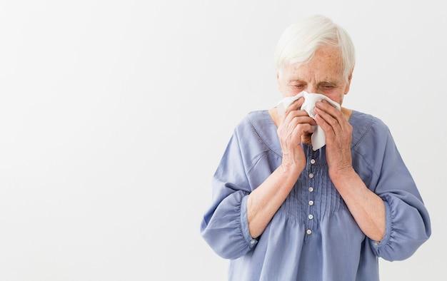 Vista frontale della donna più anziana che soffia il naso con lo spazio della copia
