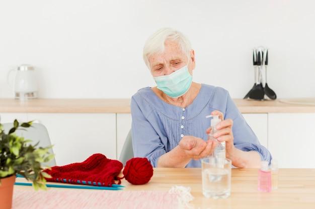 Vista frontale della donna più anziana che usando disinfettante per le mani mentre tricottando