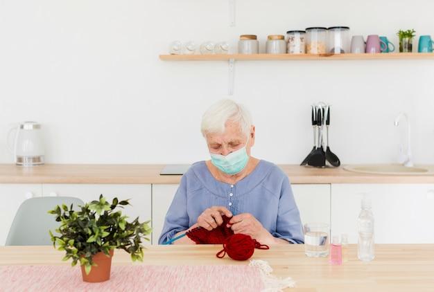 Vista frontale della donna più anziana con la maschera medica che tricotta a casa
