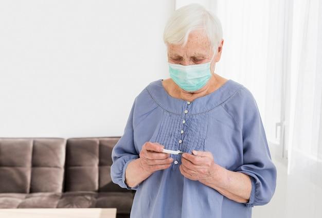 Vista frontale della donna più anziana con la mascherina medica che esamina termometro