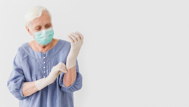 Vista frontale della donna più anziana con maschera medica e guanti chirurgici
