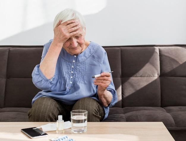 Vista frontale della donna più anziana preoccupata per la temperatura sul termometro