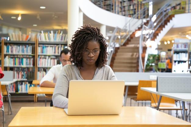 Vista frontale della donna premurosa che lavora con il computer portatile alla biblioteca