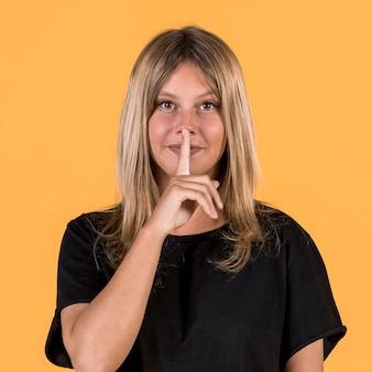 Vista frontale della donna sorda con il gesto silenzioso davanti a sfondo giallo