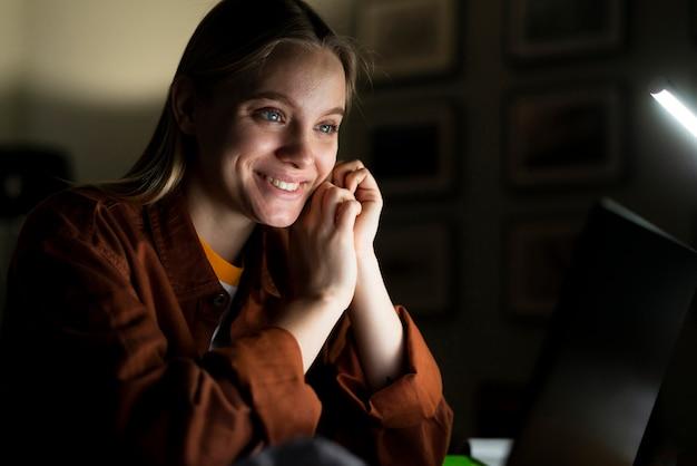 Vista frontale della donna sorridente al computer portatile
