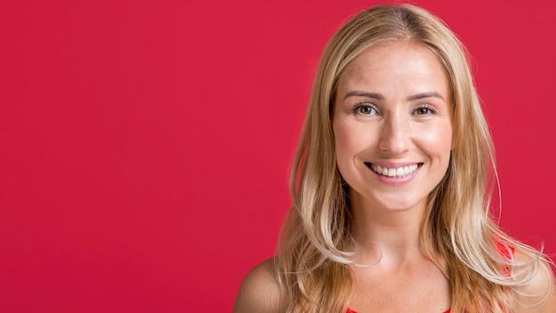 Vista frontale della donna sorridente in posa con lo spazio della copia