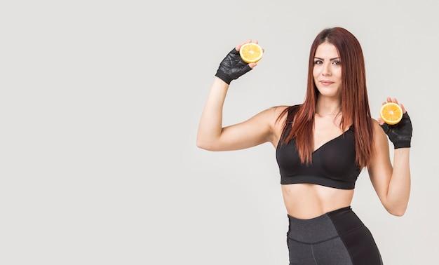 Vista frontale della donna sportiva che posa con le arance