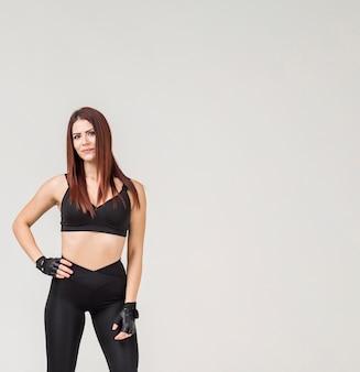 Vista frontale della donna sportiva che posa in abbigliamento della palestra